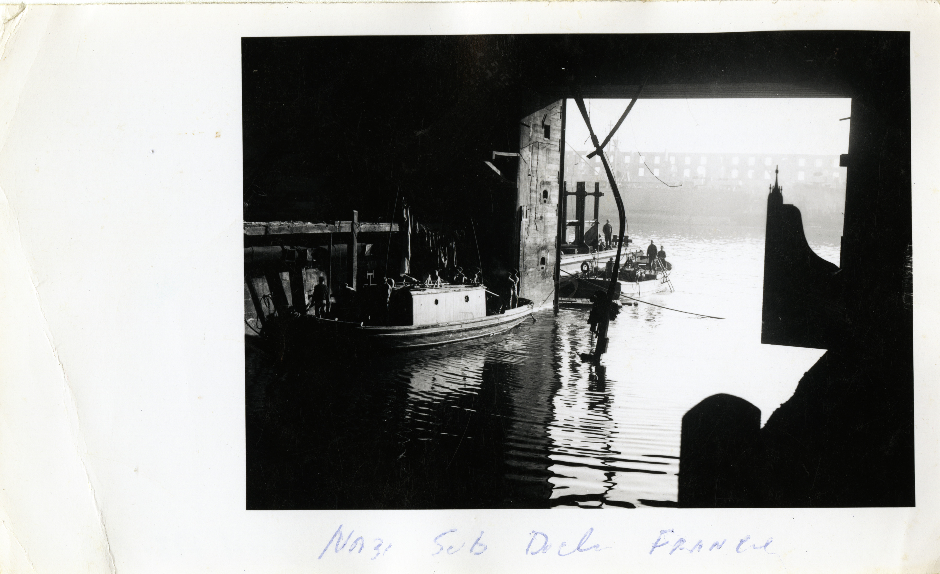 American sailors in small boats inside German submarine pen in