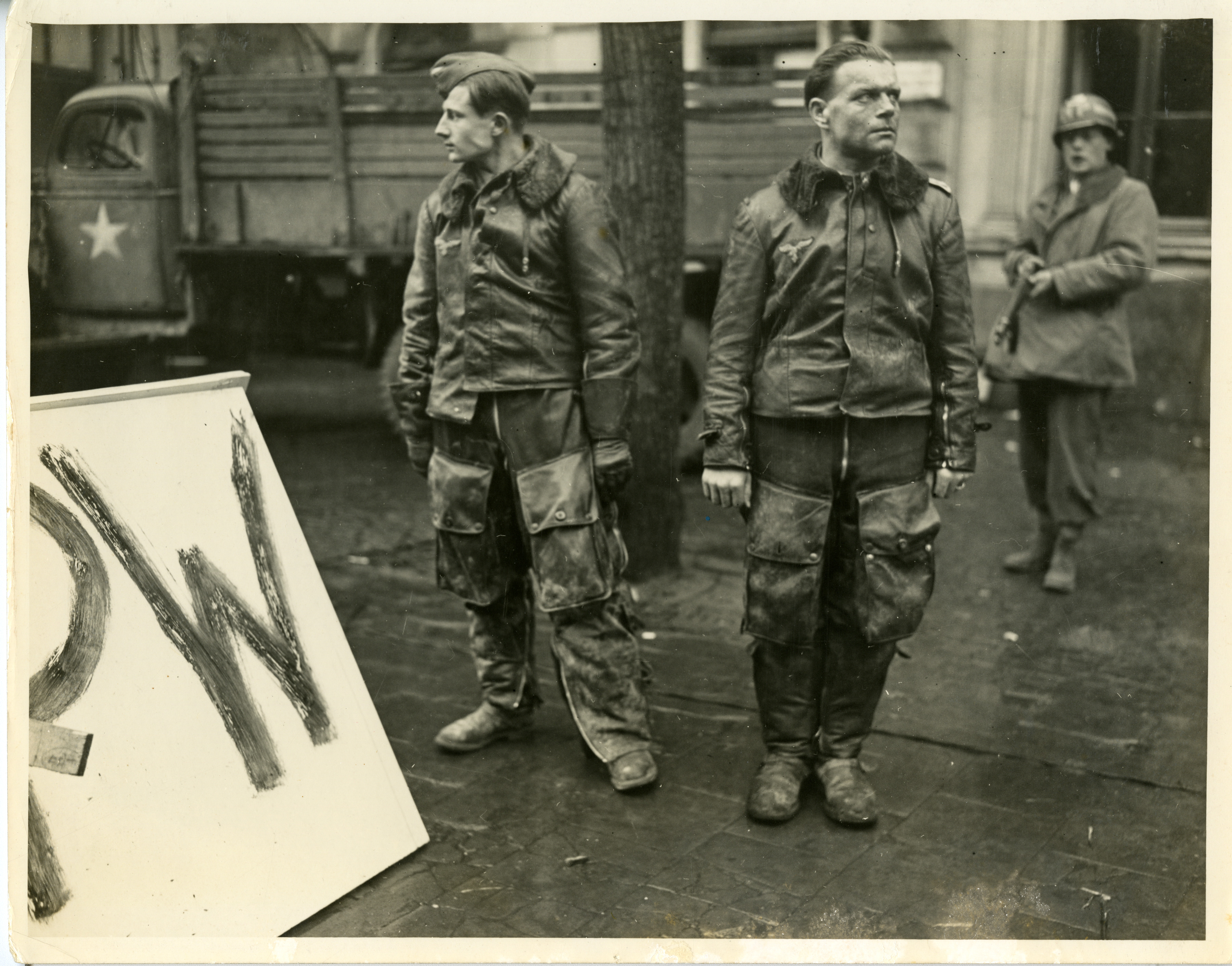 An American military police officer holds captive two Nazi pilots in
